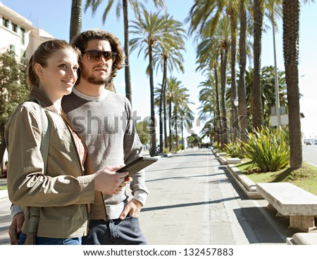 Portrait of a young tourist couple on vacation in a destination city palm trees boulevard, holding a technology tablet during a sunny day. - stock photo