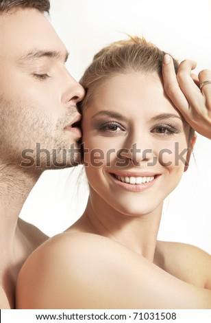Portrait of a young undressed couple on white background - stock photo