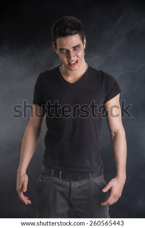Portrait of a Young Vampire Man with Black T-Shirt, Looking at the Camera, on a Dark Smoky Background. - stock photo