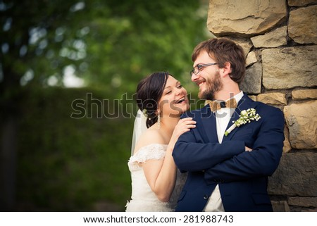 Portrait of a young wedding couple on their wedding day, looking happy, laughing together instead of posing properly for the photographer - stock photo