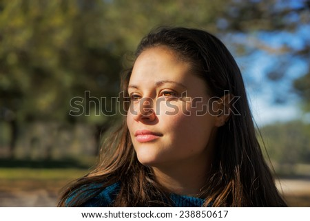 Portrait of a young white woman with brown hair and bright brown eyes outside in the sunlight looking contemplative thoughtful knowing unreadable unattainable - stock photo
