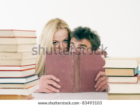 portrait of a young woman and her teacher hiding behind the books.Back to school concept. - stock photo