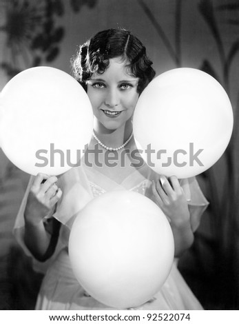 Portrait of a young woman balancing balloons on her hands and knees - stock photo