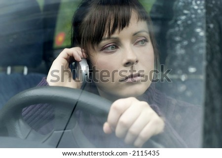 portrait of a young woman, brunette in a car making a phonecall-close up - stock photo