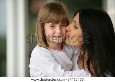 Portrait of a young woman carrying and kissing a little girl - stock photo