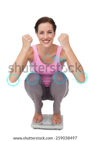 Portrait of a young woman cheering on weight scale against fitness interface - stock photo