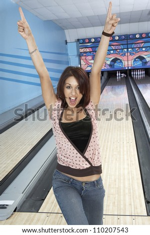 Portrait of a young woman cheers with arm raised at bowling alley - stock photo