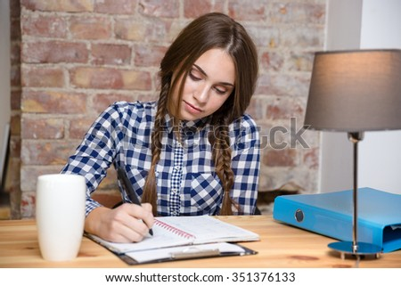 Portrait of a young woman doing her homework at home  - stock photo