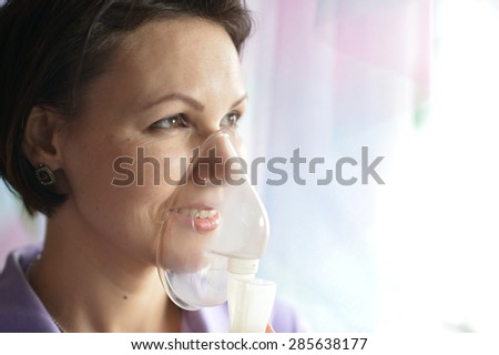 Portrait of a young woman doing inhalation at home - stock photo