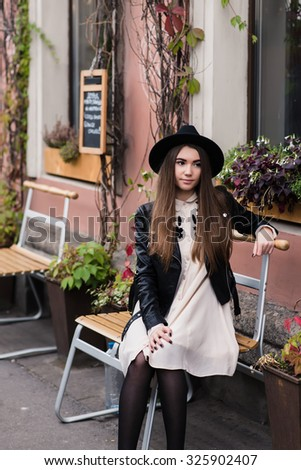 Portrait of a young woman dressed in cool trendy clothes sitting on a street chair near building with pots of flowers, stylish model with long brunette hair posing outdoors in a cool autumn day  - stock photo