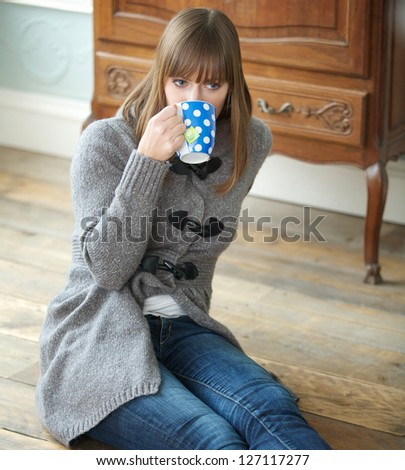Portrait of a young woman drinking a cup of coffee indoors - stock photo