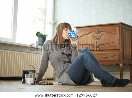 Portrait of a young woman drinking a cup of tea and relaxing - stock photo