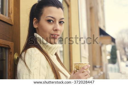 Portrait of a young woman drinking coffee outside the cafe. - stock photo
