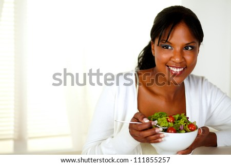 Portrait of a young woman eating healthy salad at home indoor. With copyspace. - stock photo