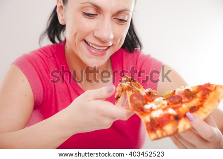 Portrait of a young woman eating pizza. - stock photo