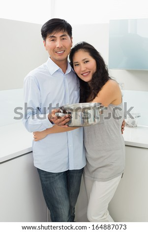 Portrait of a young woman embracing man in the kitchen at home - stock photo
