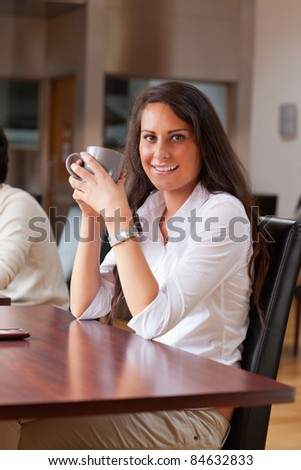 Portrait of a young woman having a coffee in a cafe - stock photo