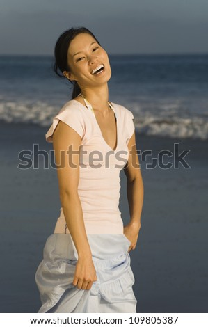 Portrait of a young woman having a good time on beach - stock photo