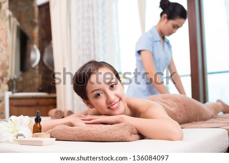 Portrait of a young woman having spa massage on the foreground - stock photo