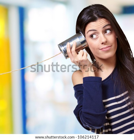 portrait of a young woman hearing through a tin can indoor - stock photo