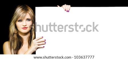 Portrait of a young woman holding and displaying large blank billboard during a advertising and marketing campaign, image over black background - stock photo