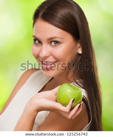 Portrait Of A Young Woman Holding Green Apple against a nature background - stock photo