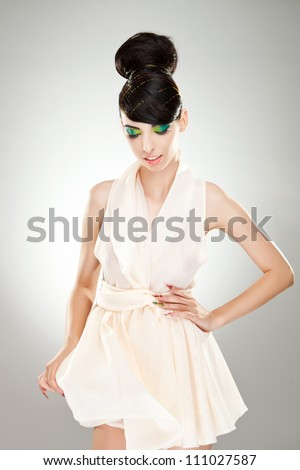 Portrait of a young woman holding her cute white dress and one hand on her waist, while looking down - stock photo