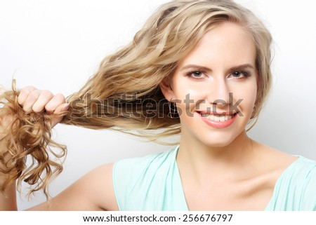 portrait of a young woman holding her long curly healthy hair - stock photo