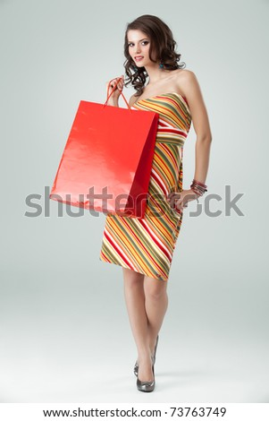 portrait of a young woman holding in one hand a red shopping bag and the other one on her hip. she is laughing and looking very happy. - stock photo