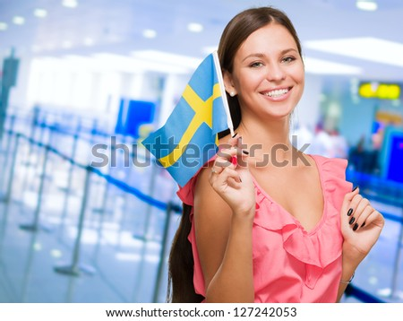 Portrait Of A Young Woman Holding Swedish Flag at an airport - stock photo