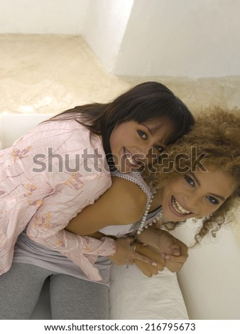 Portrait of a young woman hugging her friend - stock photo