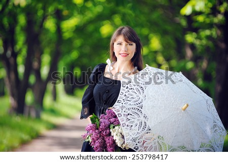 portrait of a young woman in a spring park with an umbrella. - stock photo