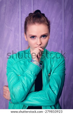 Portrait of a young woman in blue jacket on a purple background - stock photo