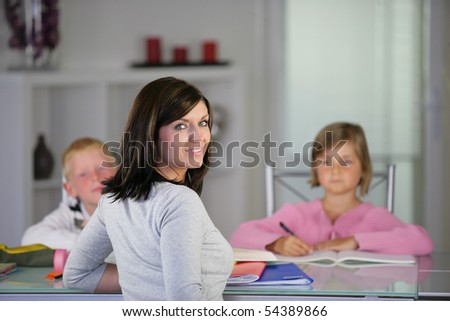 Portrait of a young woman in front of children doing homework - stock photo