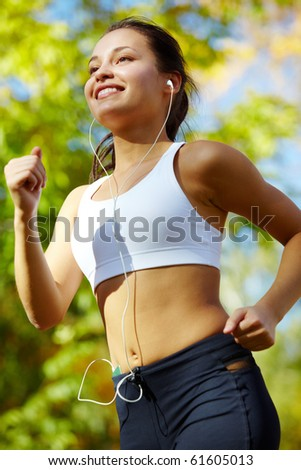 Portrait of a young woman jogging with a player - stock photo