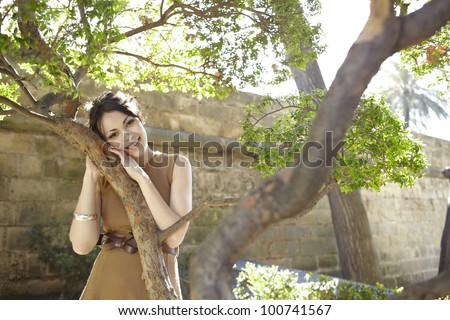 Portrait of a young woman leaning her head on a tree in the park, smiling at camera. - stock photo