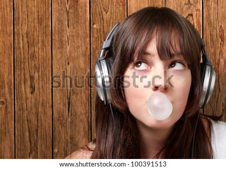 portrait of a young woman listening to music with bubble gum against a wooden wall - stock photo