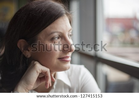 Portrait of a young woman looking away from the camera - stock photo
