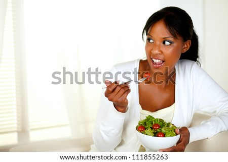 Portrait of a young woman looking right as she eats her green salad at home indoor. With copyspace. - stock photo