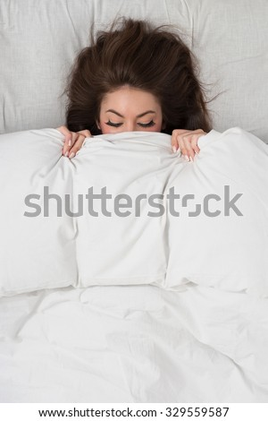 Portrait of a young woman lying in bed hiding under duvet with closed eyes. - stock photo