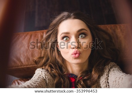 Portrait of a young woman lying on the sofa and making selfie photo while kissing at camera - stock photo