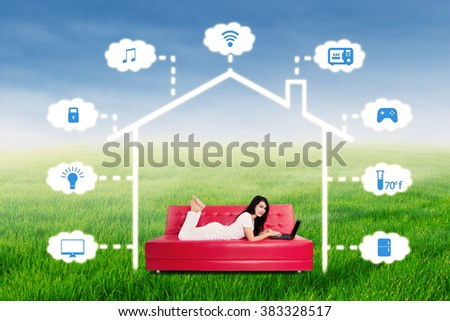 Portrait of a young woman lying on the sofa while using laptop computer to control online home automation system - stock photo