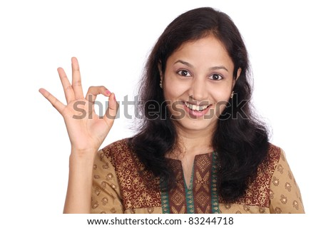Portrait of a young woman making OK gesture against white background - stock photo