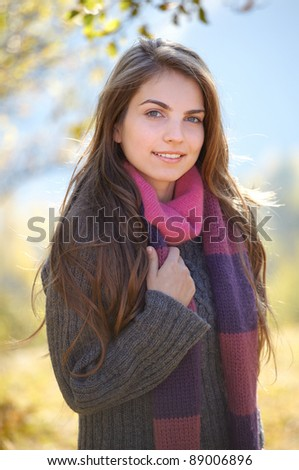 Portrait of a young woman on a chilly sunny day of autumn outdoor. - stock photo