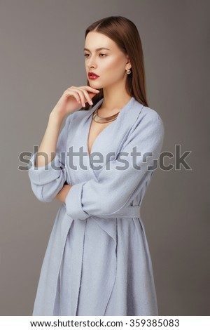 Portrait of a young woman on a gray background. - stock photo