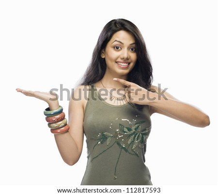 Portrait of a young woman pointing - stock photo