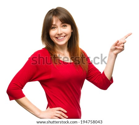 Portrait of a young woman pointing to the right using her index finger, isolated over white - stock photo