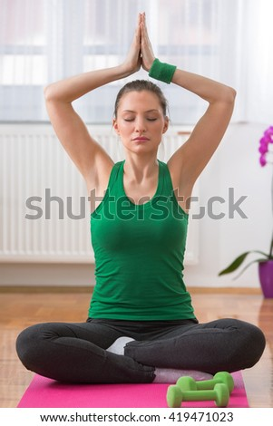 Portrait of a young woman practicing yoga at home. She is sitting cross-legged on the floor and doing breathing exercise with her arms above her head. - stock photo