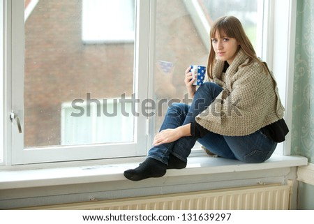 Portrait of a young woman relaxing by window with a cup of tea - stock photo