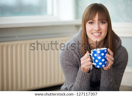 Portrait of a young woman relaxing indoors with a cup of coffee - stock photo